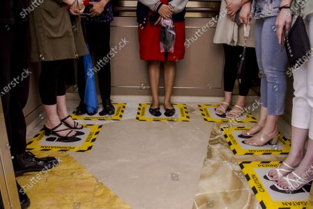 People stand on the special boxes to ensure social distancing inside an elevator at a shopping mall in Surabaya, East Java, Indonesia, 18 March 2020. Indonesia has confirmed 227 coronavirus cases with 19 deaths.