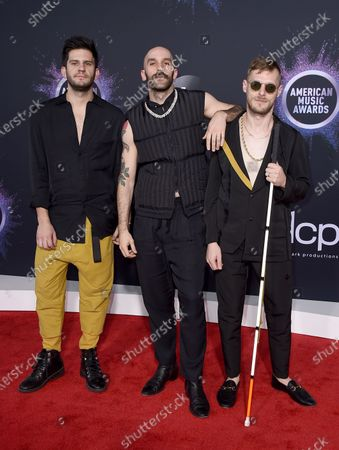Adam Levin, from left, Sam Harris, and Casey Harris, of X Ambassadors, arrive at the American Music Awards in Los Angeles. The rock trio X Ambassadors have been bouncing around the world as several of their concert dates were canceled due to the coronavirus. First was China. Then Milan. And while setting up in Poland for a performance, they were told to shut down. They eventually arrived in Lithuania and made it home to Los Angeles on Thursday as President Donald Trump announced a travel ban