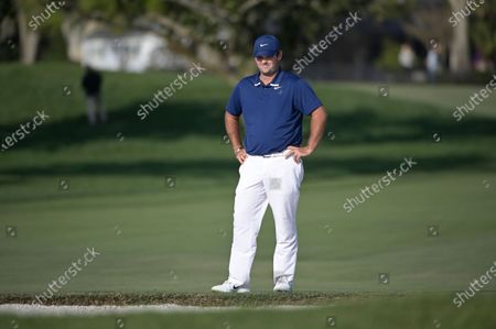 Patrick Reed checks his ball in a bunker next to the 15th green during the third round of the Arnold Palmer Invitational golf tournament, in Orlando, Fla
