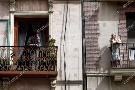 Two neighbors chat from their balconies during another day of isolation in Madrid, Spain, 19 March 2020. Spanish faces its fifth day of lockdown to contain the spreading of coronavirus outbreak.