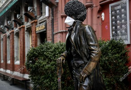 Stock Image of A view of the statue of Phil Lynott with a mask on as a result of the Coronavirus Epidemic