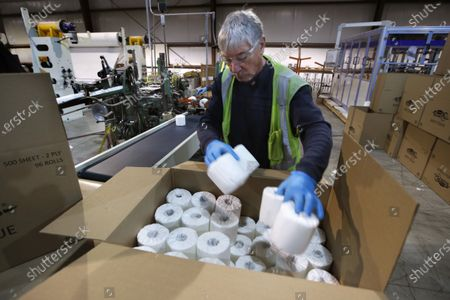 Scott Mitchell fills a box with toilet paper at the Tissue Plus factory, in Bangor, Maine. The new company has been unexpectedly busy because of the shortage of toilet paper brought on by hoarders concerned about the coronavirus