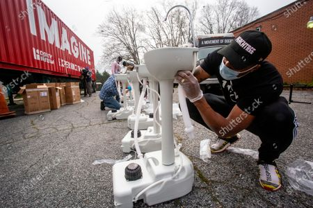 Grammy award-winning hip hop recording artist Lecrae assembles a portable wash station on in College Park, Georgia. The wash stations were distributed by Lecrae and volunteers with Love Beyond Walls, a non-profit, throughout Atlanta in areas with a high density of homeless persons