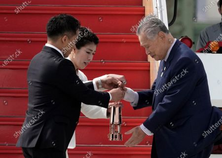 Japanese Olympic judo champion Tadahiro Nomura (L) and Olympic women's wrestling champion Saori Yoshida (2-L) hand the Olympic flame to Yoshiro Mori, Tokyo 2020 Olympic Committee President, during the Olympic flame arrival Ceremony at Japan Air Self-Defense Force Matsushima Air Base in Higashimatsushima, northern Japan, 20 March 2020. The Tokyo 2020 Olympic Flame Arrival Ceremony was scaled down over fears of coronavirus. Japanese Prime Minister Shinzo Abe is still considering holding the Tokyo Olympics as scheduled despite the current coronavirus pandemic.