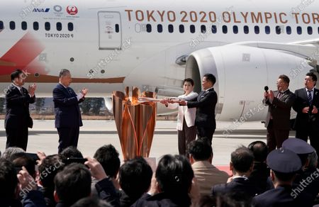 Japanese Olympic judo champion Tadahiro Nomura (3-R) and Olympic women's wrestling champion Saori Yoshida (4-R) light the Olympic flame on a cauldron during the Olympic flame arrival Ceremony at Japan Air Self-Defense Force Matsushima Air Base in Higashimatsushima, northern Japan, 20 March 2020. The Tokyo 2020 Olympic Flame Arrival Ceremony was scaled down over fears of coronavirus. Japanese Prime Minister Shinzo Abe is still considering holding the Tokyo Olympics as scheduled despite the current coronavirus pandemic.