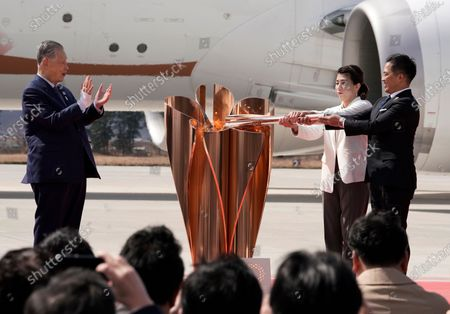 Japanese Olympic judo champion Tadahiro Nomura (R) and Olympic women's wrestling champion Saori Yoshida (2-R) light the Olympic flame on a cauldron during the Olympic flame arrival Ceremony at Japan Air Self-Defense Force Matsushima Air Base in Higashimatsushima, northern Japan, 20 March 2020. The Tokyo 2020 Olympic Flame Arrival Ceremony was scaled down over fears of coronavirus. Japanese Prime Minister Shinzo Abe is still considering holding the Tokyo Olympics as scheduled despite the current coronavirus pandemic.