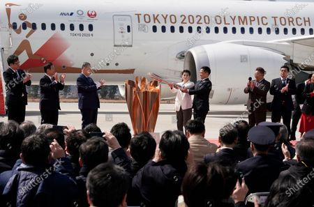 Japanese Olympic judo champion Tadahiro Nomura (5-L) and Olympic women's wrestling champion Saori Yoshida (4-L) light the Olympic flame on a cauldron during the Olympic flame arrival Ceremony at Japan Air Self-Defense Force Matsushima Air Base in Higashimatsushima, northern Japan, 20 March 2020. The Tokyo 2020 Olympic Flame Arrival Ceremony was scaled down over fears of coronavirus. Japanese Prime Minister Shinzo Abe is still considering holding the Tokyo Olympics as scheduled despite the current coronavirus pandemic.