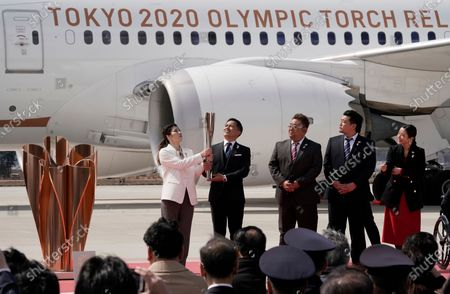Japanese Olympic judo champion Tadahiro Nomura (2-L) and Olympic women's wrestling champion Saori Yoshida (L) carry the Olympic flame during the Olympic flame arrival Ceremony at Japan Air Self-Defense Force Matsushima Air Base in Higashimatsushima, northern Japan, 20 March 2020. The Tokyo 2020 Olympic Flame Arrival Ceremony was scaled down over fears of coronavirus. Japanese Prime Minister Shinzo Abe is still considering holding the Tokyo Olympics as scheduled despite the current coronavirus pandemic.
