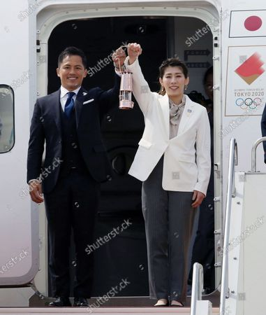 Japanese Olympic judo champion Tadahiro Nomura (L) and Olympic women's wrestling champion Saori Yoshida (R) raise the Olympic flame on a special lantern carried on a chartered flight from Greece, during the Olympic flame arrival Ceremony at Japan Air Self-Defense Force Matsushima Air Base in Higashimatsushima, northern Japan, 20 March 2020. The Tokyo 2020 Olympic Flame Arrival Ceremony was scaled down over fears of coronavirus. Japanese Prime Minister Shinzo Abe is still considering holding the Tokyo Olympics as scheduled despite the current coronavirus pandemic.