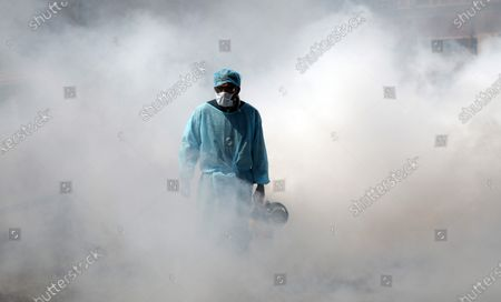 A Jammu Municipal Corporation health worker sprays disinfectant in a deserted market street after authorities ordered the closure of all shops, except medicines and groceries, to curb the coronavirus pandemic, in Jammu, India, 20 March 2020. All existing Indian visas issued to nationals of any country except those issued to diplomats, officials, UN/International organizations, employment, project visas stand suspended until 15 April 2020. All incoming travelers, including Indian nationals, arriving from or having visited China, Italy, Iran, South Korea, France, Spain and Germany after 15 February 2020 face a 14-day quarantine period.