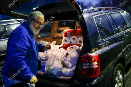 Customer Joseph Nathan loads toilet paper into the trunk of his car at a Stop & Shop supermarket that opened special morning hours to serve people 60-years and older due to coronavirus concerns, in Teaneck, N.J. For most people, COVID-19, the disease caused by the new coronavirus, causes only mild or moderate symptoms, such as fever and cough. For some, especially older adults and people with existing health problems, it can cause more severe illness, including pneumonia