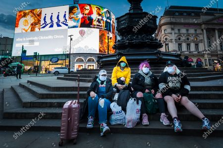 Four women wearing face masks sit on the steps of the Eros statue in Piccadilly Circus in London, Britain, 20 March 2020. British Prime Minister Johnson has ordered cafes, pubs, bars, restaurants and gyms to close tonight to mitigate the spread of the coronavirus Covid-19 pandemic.