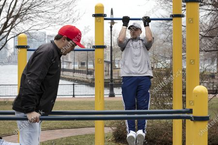 Stock Image of Michael Gill, left, and Andres Restrepo exercise in Piers Park in Boston, Friday, March, 20, 2020. The gym they usually use is closed due to the coronavirus