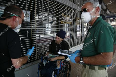 The Miami-Dude County Homeless Trust's chair, Ron Book, left, accompanied the City of Miami Homeless Services Division assistant program administrator Lazaro Trueba, right, talk to a homeless man about washing his hands during the COVID-19 virus outbreak in downtown Miami, on
