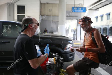 As a people pass by in a truck the Miami-Dude County Homeless Trust's chair, Ron Book, left, gives a homeless man information on the COVID-19 virus and about washing his hands during the outbreak in downtown Miami, on