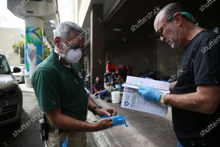 The Miami-Dude County Homeless Trust's chair, Ron Book, right, accompanied the City of Miami Homeless Services Division assistant program administrator Lazaro Trueba, left, prepare to give supplies to homeless people during the COVID-19 virus outbreak in downtown Miami, on