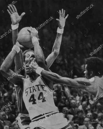 Stock Picture of David Thompson (44) of North Carolina State, has his arms hooked by UCLA's Tommy Curtis, right, while driving in for a shot at the basket during semi-final play at the NCAA championship in Greensboro, N.C., . UCLA's Keith Wilkes has his arms up in back of Thompson. North Carolina State won 80-77 in double overtime and will play Marquette in the Monday night finals
