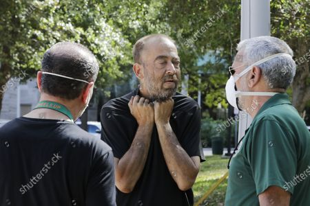 The Miami-Dude County Homeless Trust's chair, Ron Book, left, accompanied the City of Miami Homeless Services Division assistant program administrator Lazaro Trueba, right, talk to a homeless man about washing his hands during the COVID-19 virus outbreak at Bayfront Park in Miami, on