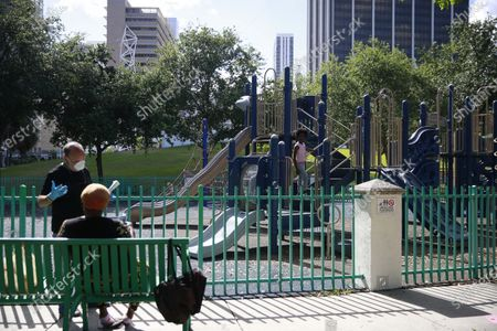 Ron Book, chair of the Miami-Dade County Homeless Trust talks to a mother about her child playing in a closed playground amid the COVID-19 virus outbreak near Bayfront Park in Miami on