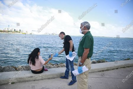 The Miami-Dude County Homeless Trust's chair, Ron Book, center, accompanied the City of Miami Homeless Services Division assistant program administrator Lazaro Trueba, right, talk to a woman about washing her hands during the COVID-19 virus outbreak at Bayfront Park in Miami, on