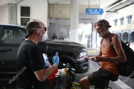 Stock Picture of As people pass by in a truck, Miami-Dude County Homeless Trust's chairman, Ron Book, left, gives a homeless man information on the COVID-19 virus and about washing his hands during the outbreak, in downtown Miami