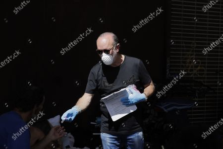 Stock Photo of The Miami-Dade County Homeless Trust's chairman, Ron Book, center, gives out hand sanitizer and information on the coronavirus to a homeless person in downtown Miami