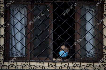 A young woman looks out a window in Managua, Nicaragua, 21 March 2020. Nicaragua has confirmed two cases of COVID-19, spread by a coronavirus.