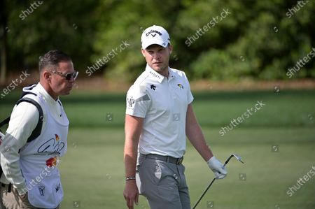 Danny Willett, right, of England, talks to his caddie, Sean Foley, while walking on the first fairway during the final round of the Arnold Palmer Invitational golf tournament, in Orlando, Fla