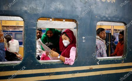 A girl sits on a train and reads a newspaper as she wear a protective mask at the Kamlapur Railway Station in Dhaka, Bangladesh, 22 March 2020. According to local media reports, Bangladesh has confirmed a second death and 24 cases of COVID-19.