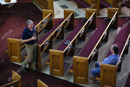 Pastor Chris Bullock (L) of the Central Presbyterian Church talks with John Williams (R) before starting worship services to stream via his phone in a near empty church in Mobile, Alabama, USA, 22 March 2020. Many churches in Alabama have closed to web only services or limited the number who can attend in person help prevent the spread of the Coronavirus Covid-19 outbreak. Countries around the world are taking increased measures to stem the widespread of the SARS-CoV-2 coronavirus which causes the Covid-19 disease.