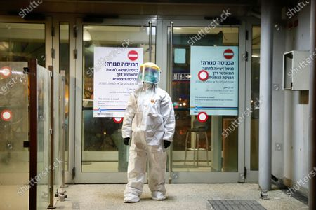 A municipality worker blocks the door as a firefighter sprays disinfectant as a precaution against the coronavirus at the Moshe Dayan Railway Station in Rishon LeTsiyon, Israel