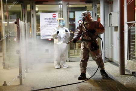 A firefighter sprays disinfectant as a precaution against the coronavirus at the Moshe Dayan Railway Station in Rishon LeTsiyon, Israel