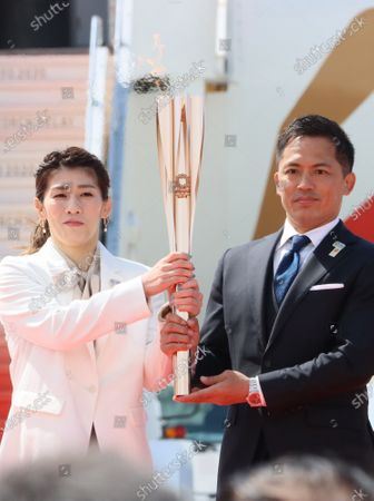 Stock Image of Olympic gold medalists Saori Yoshida (L) of wrestling and Tadahiro Nomura (R) of judo hold a torch as they attend the arrival ceremony for the Olympic flame at the Matsushima air base in Higashi Matsushima in Miyagi prefecture, northern Japan on Friday, March 20, 2020. Tokyo 2020 Olympic Games will start from March 26 at Fukushima prefecture.