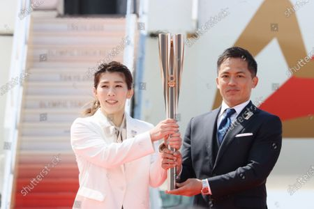 Stock Photo of Olympic gold medalists Saori Yoshida (L) of wrestling and Tadahiro Nomura (R) of judo hold a torch as they attend the arrival ceremony for the Olympic flame at the Matsushima air base in Higashi Matsushima in Miyagi prefecture, northern Japan on Friday, March 20, 2020. Tokyo 2020 Olympic Games will start from March 26 at Fukushima prefecture.