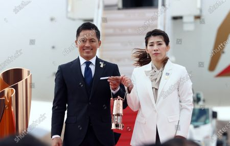 Olympic gold medalists Saori Yoshida (R) of wrestling and Tadahiro Nomura (L) of judo hold a lantern of Olympic flame as they attend the arrival ceremony for the Olympic flame at the Matsushima air base in Higashi Matsushima in Miyagi prefecture, northern Japan on Friday, March 20, 2020. Tokyo 2020 Olympic Games will start from March 26 at Fukushima prefecture.