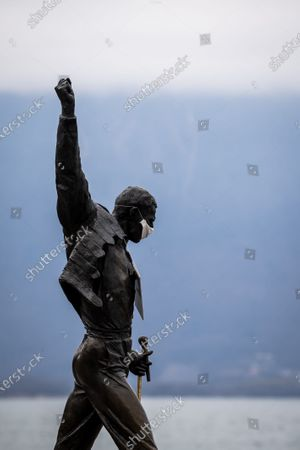 The statue of Freddie Mercury is adorned with the additional feature of a surgical mask and a sign reading 'stay home', during the coronavirus disease (COVID-19) outbreak in Montreux, Switzerland, 23 March 2020.
