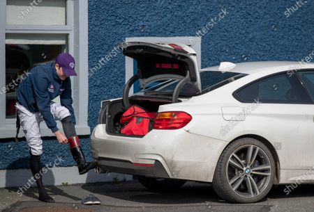 Jockey Emmet McNamara gets changed out of the back of his car as jockeys endeavour to maintain social distancing at the racecourse