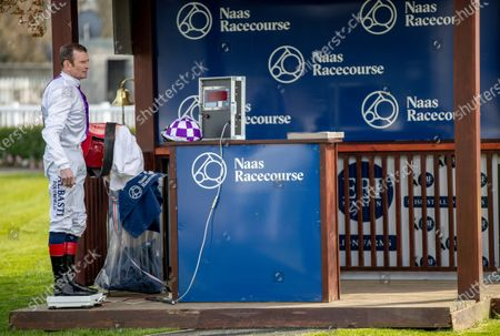 Kevin Manning weighs in outside in the parade ring in an attempt to keep a social distance from their fellow jockeys