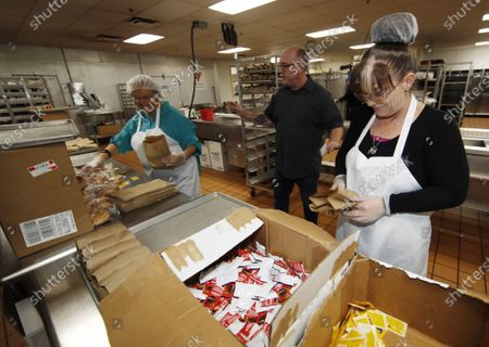 Rich Anderson, center, associate director at the branch of the Volunteers of America, helps Mary Machin, left, and Kortnie Gardner as they prepare bags of lunch as daily demands for food increase while most vulnerable individuals and families shelter inside to reduce the spread of the coronavirus, in Denver. According to the World Health Organization, most people recover in about three to six weeks depending on the severity of the COVID-19 illness