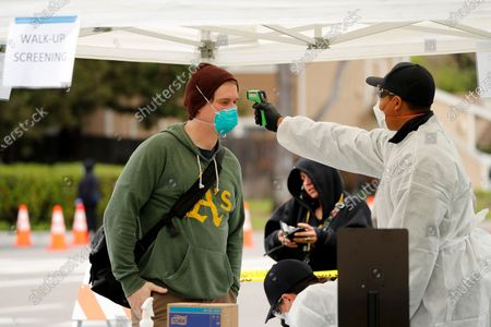 A person gets his temperature taken at a coronavirus testing center at the Hayward Fire Station #7 in Hayward, California, USA, 23 March 2020. The free test facility is open to the public, no matter where they live or immigration status. The City facility annouced it is opening the facility 'so sick people, first responders, and healthcare workers with recent suspected exposures to the novel coronavirus can be test for infection'. California Governor Gavin Newsom order a state-wide shelter-in-place legal order directing their residents to stay at home, except for essential work, essential needs, such as grocery shopping, food or food services, banks, laundry, and other essential business will remain open.