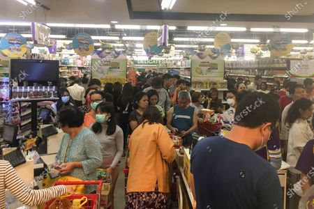 Stock Photo of People line up to buy food and other supplies at a 24-hour supermarket in Yangon, Myanmar, following the first cases of coronavirus announcement. Myanmar has announced its first two confirmed cases of COVID-19, one in the nation's biggest city, Yangon, and the other in the western state of Chin. For most people, the new coronavirus causes only mild or moderate symptoms. For some it can cause more severe illness