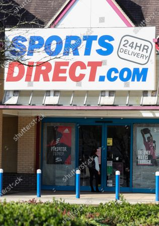 Sports Direct (Sports Direct.com) sportswear store, Isleworth, West London, closed due to Coronavirus Outbreak despite rumours of opening this morning. A person reads the notice on the shop door.