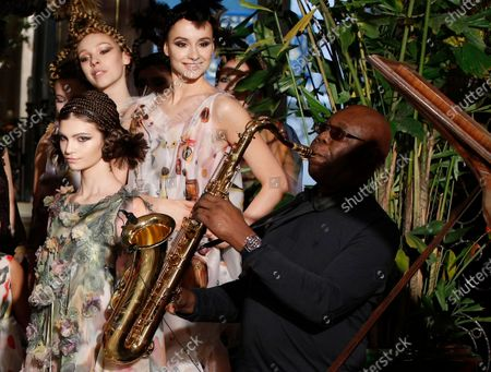 """Models present creations for Franck Sorbier's Haute Couture Spring-Summer 2018 fashion collection while saxophonist Manu Dibango performs in Paris. Renowned jazz man Manu Dibango, to many the beloved """"Papy Groove"""" who served as an inspiration and pioneer in his art, died on Tuesday from the coronavirus, his official Facebook page announced. He was 86. For most people, the new coronavirus causes only mild or moderate symptoms. For some it can cause more severe illness"""