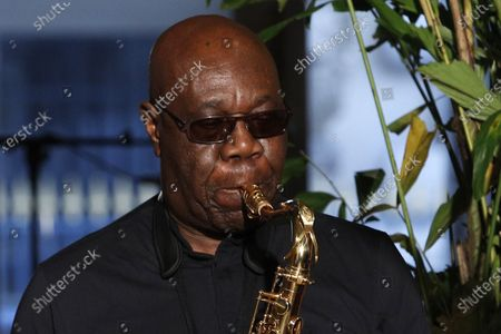 """Saxophonist Manu Dibango performs during Franck Sorbier's Haute Couture Spring-Summer 2018 fashion collection in Paris. Renowned jazz man Manu Dibango, to many the beloved """"Papy Groove"""" who served as an inspiration and pioneer in his art, died on Tuesday from the coronavirus, his official Facebook page announced. He was 86. For most people, the new coronavirus causes only mild or moderate symptoms. For some it can cause more severe illness"""