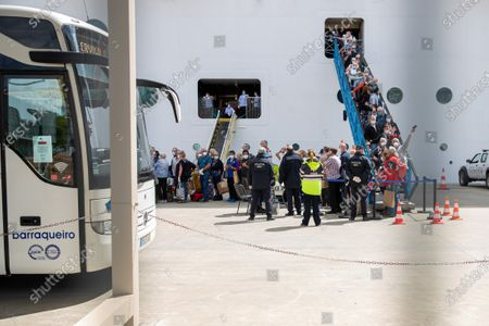 Passengers disembark from the Cruise Ship 'MSC Fantasia', that travelled from Brazil to Portugal with 1338 passengers on board, of 38 nationalities, so that they can be taken by bus to the airport and later return to their home countries,  at the Lisbon Harbour, Portugal, 24 March 2020.