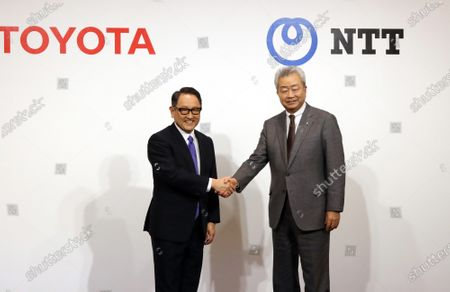 Japan's automobile giant Toyota Motor president Akio Toyoda (L) shakes hands with Japan's telecommunication giant NTT Group president Jun Sawada (R) as they announce the companies will form a business and capital alliance in Tokyo on Tuesday, March 24, 2020. They also announced to develop a smart city at the foot of Mt. Fuji, former site of Toyota's Higashi Fuji plant.