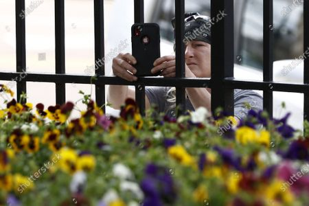 Cody Calcote uses her smartphone to take a photograph of Republican Gov. Tate Reeves as he speaks with reporters outside the Governor's Mansion to give an update on the current situation of COVID-19 and coronavirus in the state and discuss Mississippi's ongoing response to slow the spread, in Jackson, Miss
