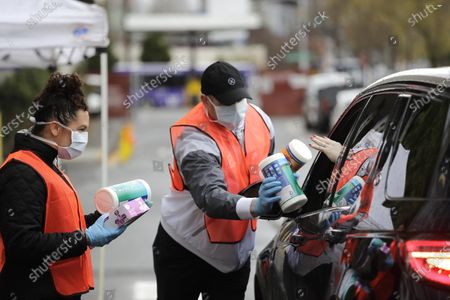 Volunteers Keshia Link, left, and Dan Peterson reach for disinfectant wipes from a driver at a drive-up donation site for medical supplies at the University of Washington to help fight the coronavirus outbreak, in Seattle