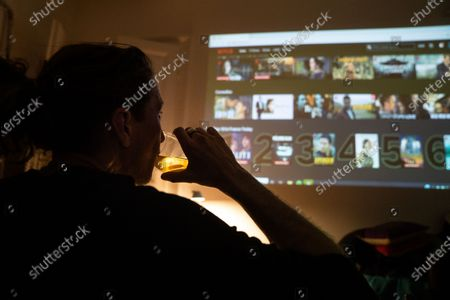 Thomas Smith, husband of Susanne Hassler-Smith, has a sip as he is following a streaming provider projection on a wall in their shared flat in Vienna, Austria, 20 March 2020 (issued 25 March 2020). Susanne Hassler-Smith, 30-year-old Austrian freelance photographer and videographer from Graz, Styria, married Thomas Smith, 34-year-old American video editor and stock trader, on 20 February 2020 in Graz, Austria. Soon after, they had to cancel their honeymoon in Venice, Italy, as the spread of the Covid-19 disease had broken out in Europe. While in the midst of moving Susanne's home from Graz to Vienna in February, they finished settling in a shared flat in Vienna a week before Covid-19 matters worsened. Susanne will apply for a Green Card, Thomas' scheduled flight back to Los Angeles was cancelled, as were many other international flights worldwide due to the global coronavirus outbreak. Susanne and Thomas begun applying for VISA extensions for his stay in the European Union to overcome the crises together. Now, they are a part of a shared flat in Vienna, together with roommates from France and Germany, whom the couple didn't know before. 'With everything as it is at the moment, we don't plan too far ahead and take each day as it comes,' Susanne says. 'We stick to the home office lifestyle and social distancing measures as instructed to help flatten the curve of this epidemic.' They keep the daily routine as normal for everyone as possible. Coffee, work, lunch, workout, dinner and from time to time they meet for a coffee in the kitchen or on the balcony on sunny days. Austrian Chancellor Kurz had announced extended restrictions concerning the movement of individuals, the closure of commercial activities and other extensions of the preventive measures aimed at slowing down the pandemic COVID-19 disease caused by the SARS-CoV-2 coronavirus, from 16 March 2020 on until at least Easter Monday, 13 April 2020.