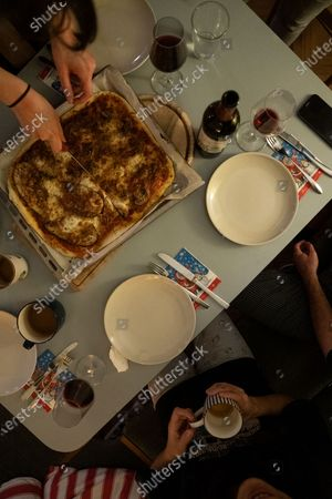 Susanne Hassler-Smith and her husband Thomas Smith eat pizza together with roommates in their shared flat in Vienna, Austria, 20 March 2020 (issued 25 March 2020). Susanne Hassler-Smith, 30-year-old Austrian freelance photographer and videographer from Graz, Styria, married Thomas Smith, 34-year-old American video editor and stock trader, on 20 February 2020 in Graz, Austria. Soon after, they had to cancel their honeymoon in Venice, Italy, as the spread of the Covid-19 disease had broken out in Europe. All while in the midst of moving Susanne's home from Graz to Vienna in the month of February, they finished settling in amongst a shared flat in Vienna a week before Covid-19 matters worsened. They had chosen Vienna, which is 'a better place for work and travel than Graz.' Susanne mentions, as a new home base for their plan to commute between Austria and the US before Susanne will apply for an American green card. Thomas' scheduled flight back to Los Angeles was soon canceled, as were many other international flights worldwide due to the global outbreak of the Coronavirus. As a result, Susanne and Thomas have begun applying for VISA extensions for his stay in the European Union to challenge the crises together. Now, they are a part of a shared flat in Austrian capital Vienna, together with roommates from France and Germany, whom the couple didn't know before. Susanne states, 'With everything as it is at the moment, we don't plan too far ahead and take each day as it comes.' In the beginning all roommates followed the news several times a day, but as of day three with the extended restrictions concerning the movement of individuals, they started to relax a bit, accept the new situation and stopped running for every push notification on their phones. Susanne continues, 'We stick to the home office lifestyle and social distancing measures as instructed to help flatten the curve of this epidemic. Since I had planned a lot of video editing work before the lock down announc